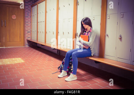 Worried student holding book while sitting on bench - Stock Photo