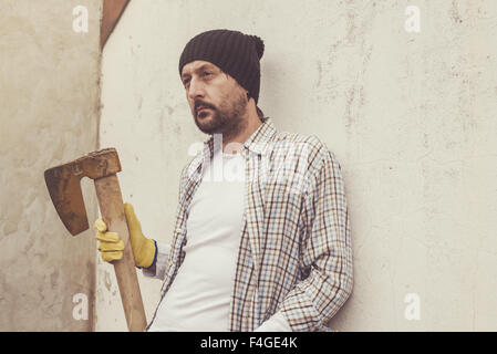 Serious confident lumberjack, adult bearded man holding a big axe in outdoors surrounding - Stock Photo