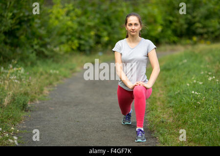 Young sporty girl warming up before Jogging in the Park. - Stock Photo