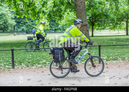 Two Police officers riding bicycles patrolling in St James's Park by The Mall, London England UK - Stock Photo