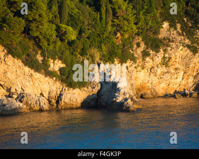 Sunset on the Dalmatian coast of the Adriatic sea makes the cliffs turn golden , here the outskirts of Dubrovnik - Stock Photo