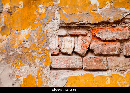 Old peeling yellow plaster wall with visible bricks