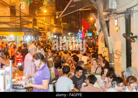 evening, Hanoi old quarter is packed in the evening with people enjoying street food and drinks at the many bars,Hanoi,Vietnam - Stock Photo