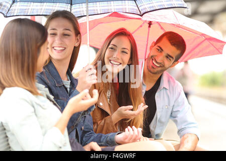 Four friends talking outdoor in a rainy day under umbrellas waiting in a train station - Stock Photo