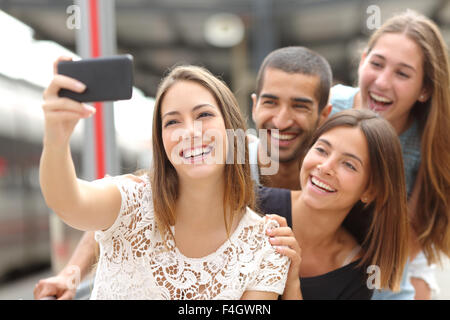 Group of four funny friends taking selfie with a smart phone in a train station in summer - Stock Photo