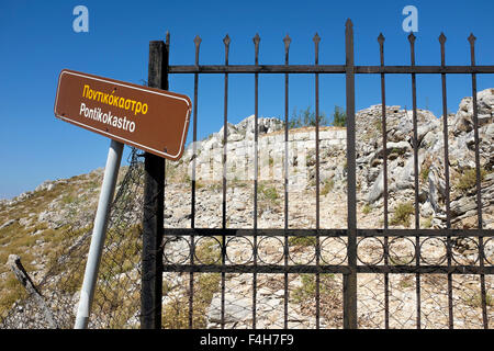 Sign marking the site of Pontikokastro, the ruined hilltop castle above the old village of Chorio, on the Greek - Stock Photo