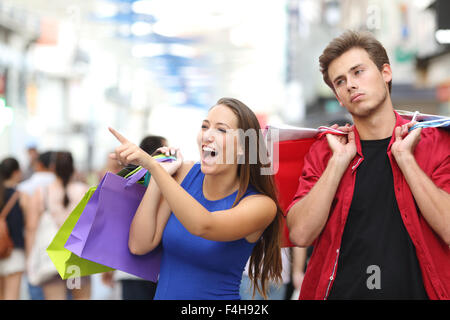 Bored man shopping with his girlfriend in a commercial street - Stock Photo