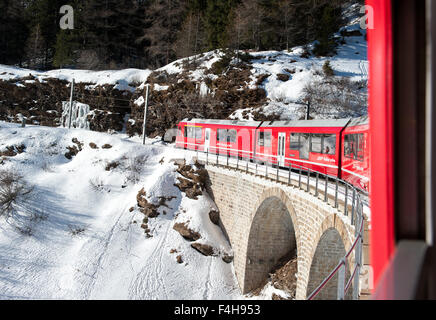 Red train of Bernina, on the Retica railway, over a bridge during its climbing to reach Saint Moritz in Switzerland - Stock Photo