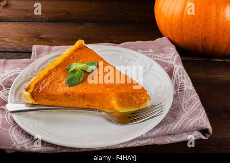 A piece of pumpkin pie with mint, white plate, fork, linen napkin on dark wooden background - Stock Photo