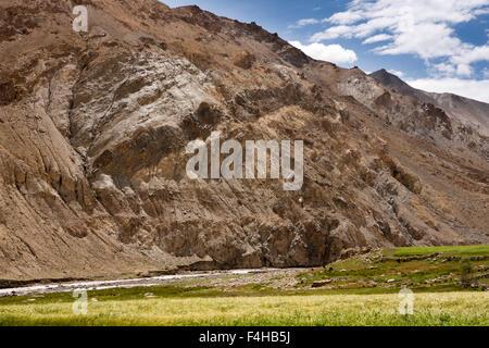 India, Jammu & Kashmir, Ladakh, Miru, Giah River flowing thrugh rocky landscape beside barley fields - Stock Photo
