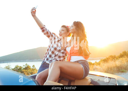 Two young beautiful girls are doing a photo of yourself in a convertible - Stock Photo