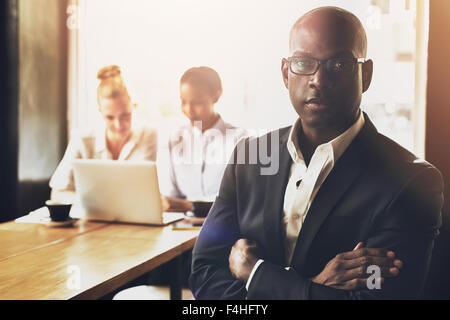 Confident succesful black business man in front of group of people - Stock Photo