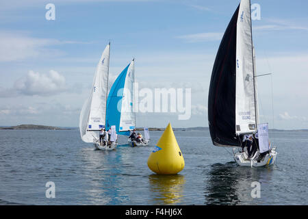 J70 class Racing sailboats on downwind course with gennaker sails  up in the light breeze - Stock Photo
