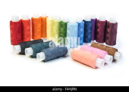 multicolored threads for sewing on spools isolated on white background