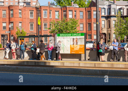 People wait for an inbound train at the Brigham Circle Station on the MBTA Huntington Avenue Line in Boston, Massachusetts. - Stock Photo