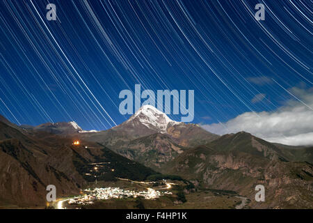 Moonlit view of star trails above Mount Kazbek (5047m), the village of Gergeti and Gergeti Trinity Church in northern - Stock Photo