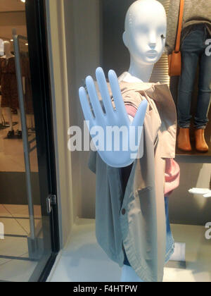 One dressed female mannequin in clothing store with stop hand symbol - Stock Photo