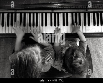 Two children (girls age 05 and 2) play music on piano. Aerial point of view - Stock Photo
