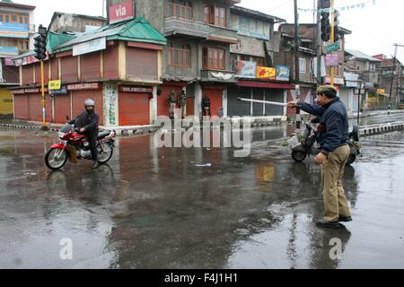 Srinagar, Kashmir. 19th Oct, 2015. A policemen stops a motercyclist  during a curfew in Srinagar, Indian-controlled. - Stock Photo