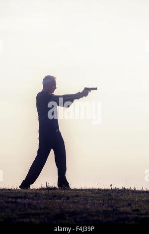 silhouette of a man with a gun - Stock Photo