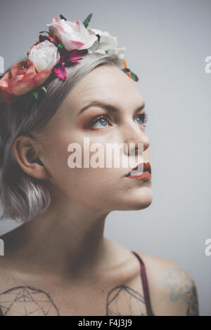 Young tattooed woman wearing a flower crown - Stock Photo