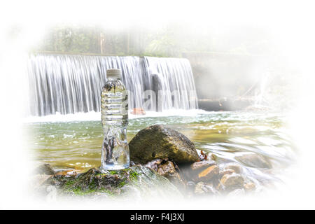 Plastic bottle with waterfall background at tropical forest - Stock Photo