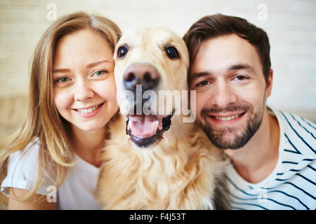 Happy couple looking at camera with dog between them - Stock Photo