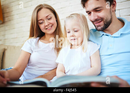 Happy young couple and their daughter reading at home - Stock Photo