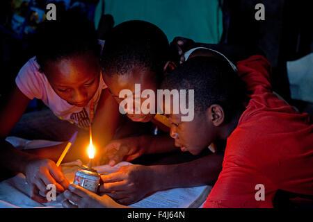 African children trying to read book with home made kerosene light Kamere Lake Naivasha Kenya - Stock Photo