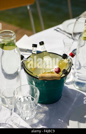 Bottles of liquor in a basket on a table ready laid, Sweden. - Stock Photo