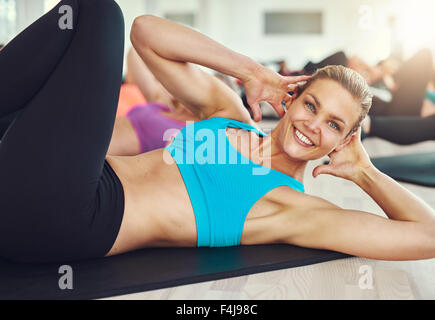 fitness, sport, training and people concept - smiling woman doing abdominal exercises on mat in gym - Stock Photo