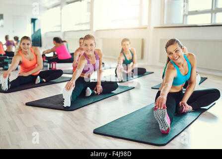 Group of young women in aerobics class at a gym doing stretching exercises to tone their muscles in a health and - Stock Photo