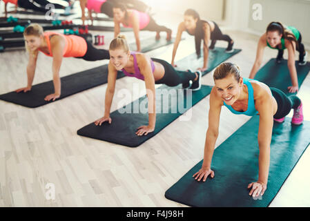 Large group of young women working out in a gym doing push ups in an aerobics class in a health and fitness concept - Stock Photo