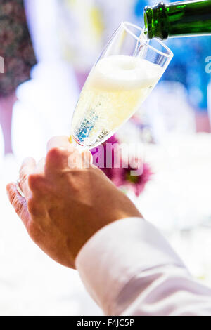 Sparkling wine being poured into a champagne flute. - Stock Photo