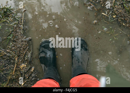 Person wearing Wellington boot standing in puddle, low section - Stock Photo