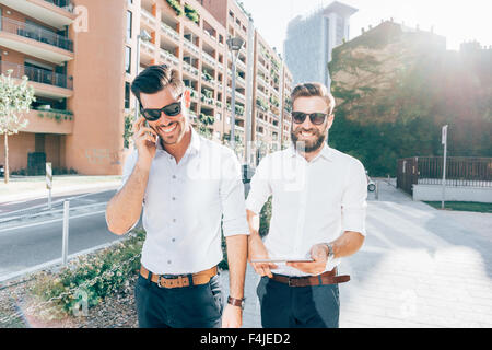 Knee figure of two young bearded blonde and black hair modern businessman, walking in the city, talking smartphone - Stock Photo
