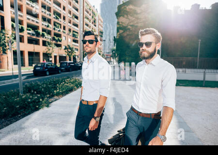 Knee figure of two young bearded blonde and black hair modern businessman, walking in the city backlight, both overlooking - Stock Photo