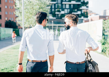 Knee figure of two young bearded blonde and black hair modern businessman, walking in the city backlight, view from - Stock Photo