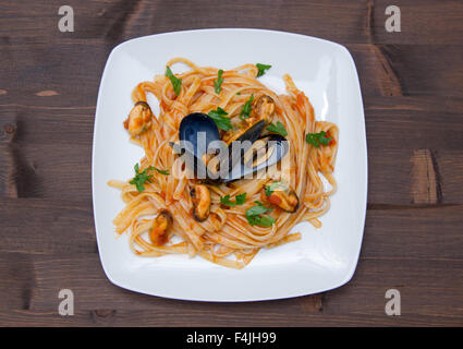 Pasta with mussels on the plate on wooden table top view - Stock Photo
