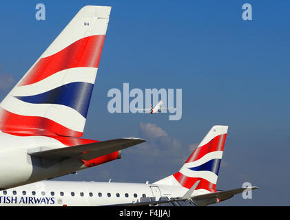 British Airways plane taking off and two BA tail fins, London City Airport, London, Britain, UK - Stock Photo