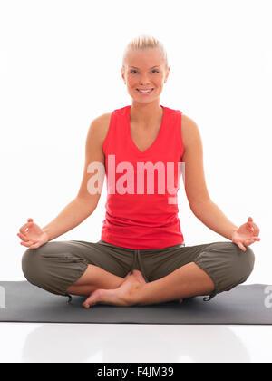 Studio portrait of teenage girl doing yoga - Stock Photo