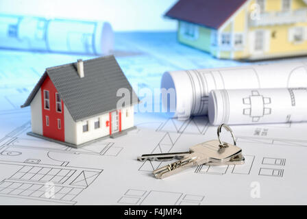 Blueprints with house keys and houses - Stock Photo