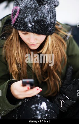 Sweden, Stockholm, girl (12-13) wearing winter coat and hat receiving text message - Stock Photo