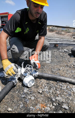 Fireman connects hoses to a water source - Stock Photo