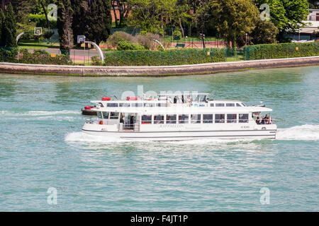 Boat full of tourists in Venice Canal - Stock Photo