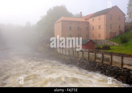 Brick building on riverbank covered with morning fog - Stock Photo