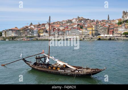 Rabelo boat, used to transport Port Wine, on the Douro river with views to the Ribeira in Porto, Portugal - Stock Photo