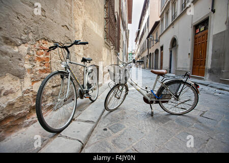two Bicycles parked on stands in empty street, Florence Italy, - Stock Photo