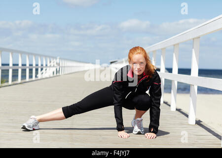 Young redhead woman exercising at pier - Stock Photo