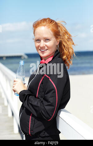 Young redhead smiling woman holding bottle of water, portrait - Stock Photo